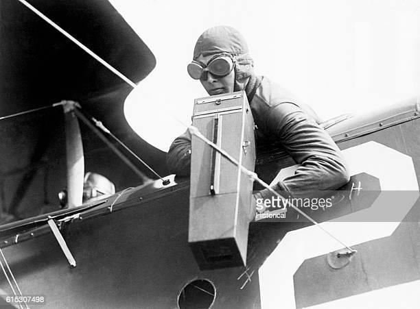 The copilot of a plane takes photograph using an Aeroplane Graflex camera in flight during World War I ca 19141918