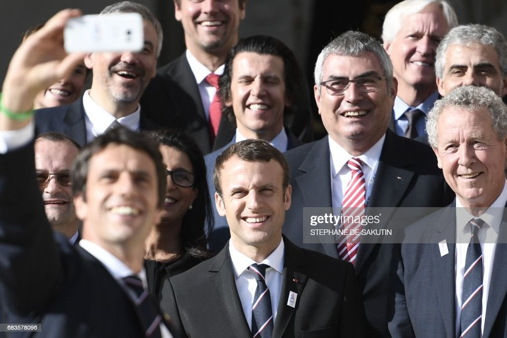 TOPSHOT - The co-president of the Paris bid for the 2024 Olympics Tony Estanguet (L, foreground) takes a selfie with new French President Emmanuel Macron (C), the president of the IOC Evaluation Commission for the 2024 Olympics Patrick Baumann (L) and French member of the IOC Guy Drut (R) at the Elysee Palace in Paris after a meeting with members of the International Olympic Committee (IOC) Evaluation Commission on May 16, 2017 prior to a vote for the 2024 Summer Olympics. /