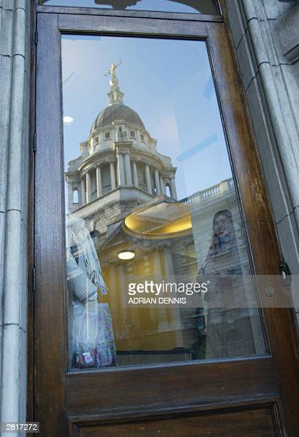 The copula of the Old Bailey courthouse is reflected in the glass of a door after Ian Huntley was sentenced to two life terms in prison for murdering...