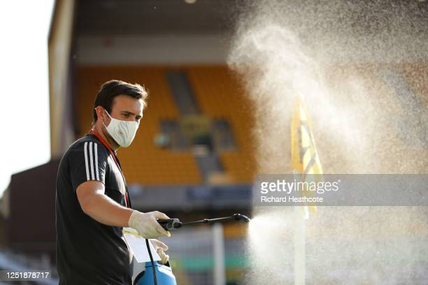 The corner flag is disinfected by a member of staff wearing gloves and a face mask during the Premier League match between Wolverhampton Wanderers...
