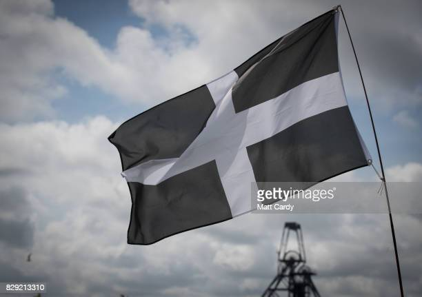 The Cornish flag flies as people listen as Labour leader Jeremy Corbyn speaks at a campaign rally at Heartlands in Camborne on August 10 2017 near...