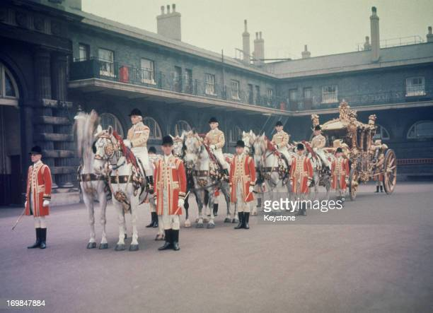 The Coronation coach drawn by horses showing the four postilions and the eight grooms London 1953 The carriage built by Samuel Butler dates from 1762...