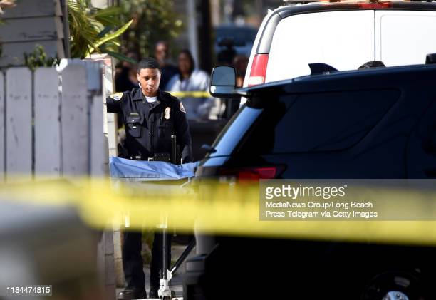 The coroner van takes the victims of a shooting that killed 3 and wounded 9 Tuesday night in the 2700 block of 7th Street near Ohio Avenue in Long...