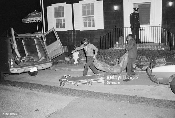 The coroner's office employees at Amityville remove a body from the home of Ronald DeFeo Sr here after the car salesman his wife two daughters and...