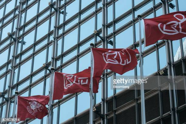 The corporate flags of Power Assets Holdings Ltd from left Cheung Kong Property Holdings Ltd CK Hutchison Holdings Ltd and CK Infrastructure Holdings...