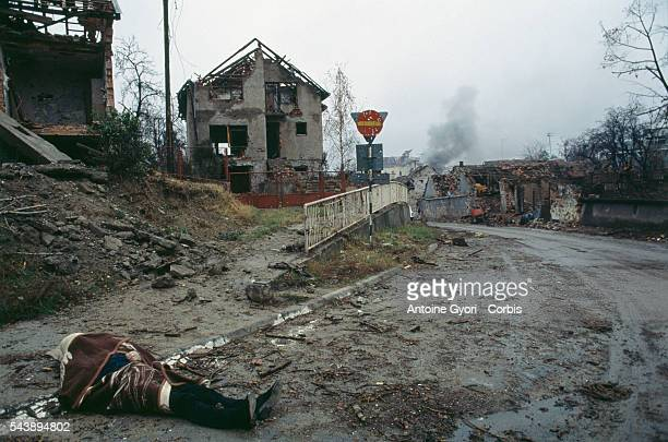 The corpse of a civilian lies in the deserted street near bombed buildings after a threemonth battle between the Croatian armed forces and the...