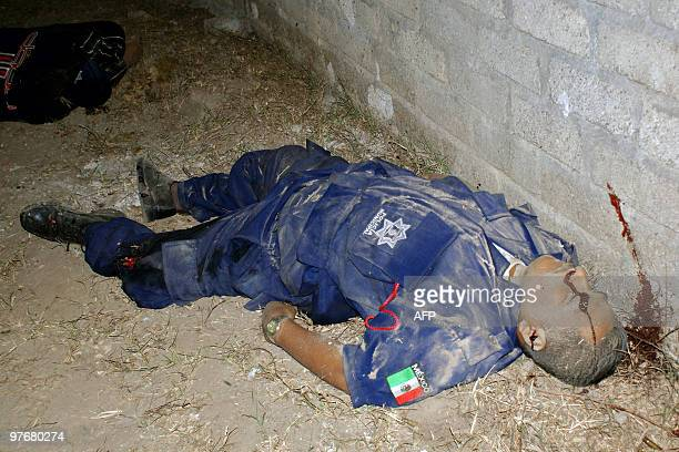 The corpse of a member of the municipal police remains on the floor in Tulcingo neighborhood Acapulco Guerrero state Mexico on March 12 2010 13...