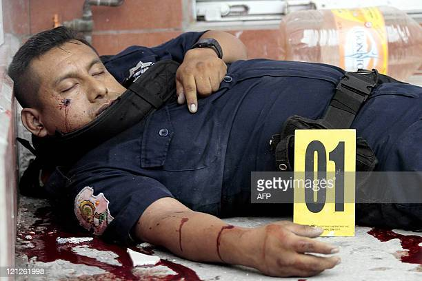 The corpse of a Mexican policeman lies at the Cuauhtemoc avenue after a shooting with gunmen on August 16 2011 in the touristic city of Acapulco...