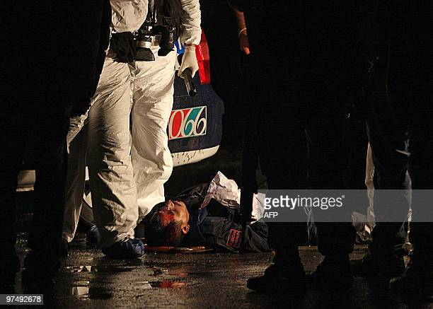 The corpse of a police officer lies on the street after a gang attack in San Nicolas de la Garza Nuevo Leon State on March 06 2010 Two members of the...