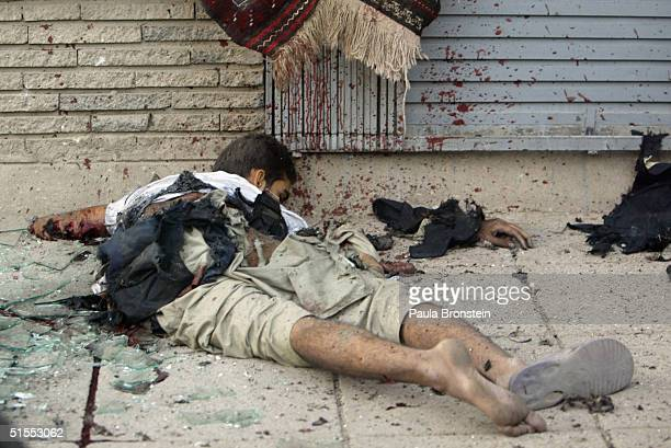 The corpse of a suicide bomber lays on a commercial shopping street October 23, 2004 in Kabul, Afghanistan. The blast killed a 12-year-old girl and...