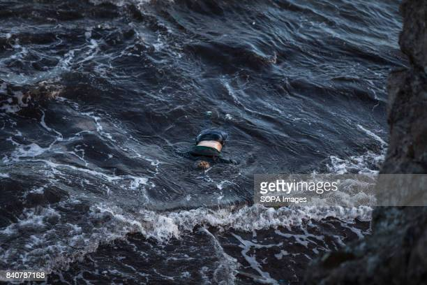 The corpse of a woman floats on the water in the Aegean Sea facing the Greek coasts Thousands of people have lost their lives making the trip as...