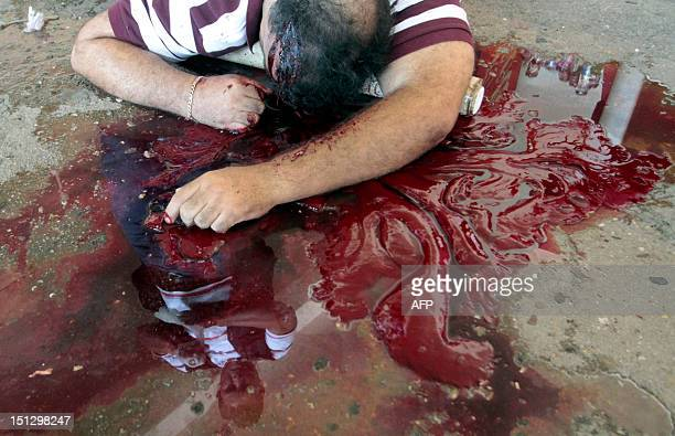 The corpse of federal police officer Victor Manuel Cadena lies on a pool of his own blood at the place where he was killed at Los Organos villages in...