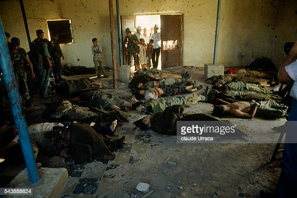 The corpses of civilians and military killed during combat between guerrilla fighters and members of the El Salvador army lie on the floor in the...