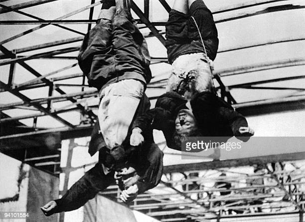 The corpses of Italian dictator Benito Mussolini and his mistress Claretta Petacci are hanged in front of a garage in Milan's Piazzale Loreto April...
