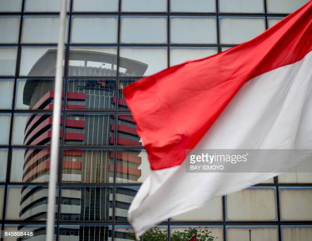 The Corruption Eradication Commission building is seen in window reflections past an Indonesian national flag in Jakarta on September 12 2017...