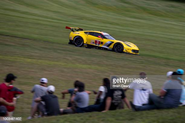 The Corvette C7R of Jan Magnussen of Denmark and Antonio Garcia of Spain races past a group od spectators during the IMSA WeatherTech Series race at...