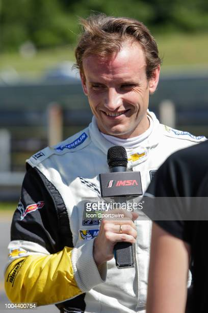 The Corvette Racing Corvette C7R driver Antonio Garcia talks to reporter after winning GTLM qualifying prior to the IMSA Northeast Grand Prix on July...