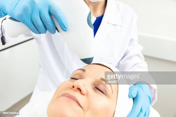 the cosmetologist is caring for the patient's face - beauty salon ukraine stock pictures, royalty-free photos & images