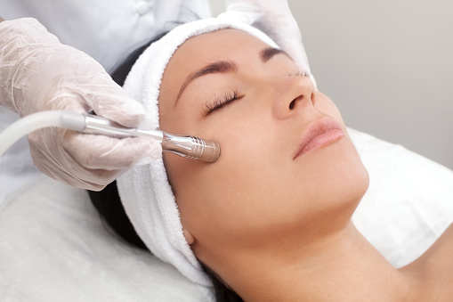 The cosmetologist makes the procedure Microdermabrasion of the facial skin of a beautiful, young woman in a beauty salon 899611236