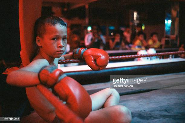 The country is enjoying a boom in tourism and Thai boxing is shown everywhere Here at a Pattaya bar clients gather round a boxing ring to watch child...