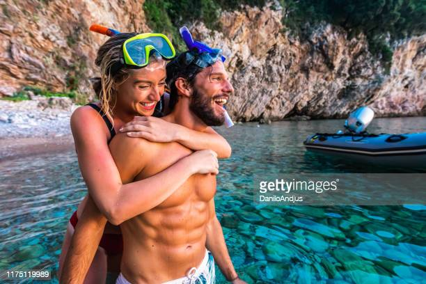 the couple have fun before snorkelling in the sea - snorkeling stock pictures, royalty-free photos & images