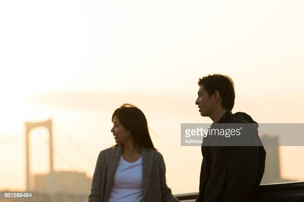The couple is talking at sunset.