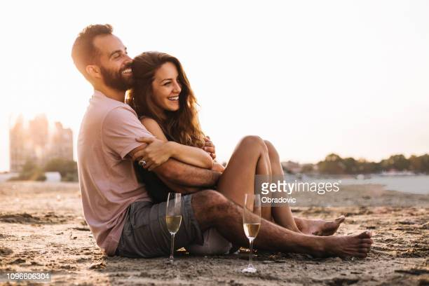 the couple  on the beach celebrate their love with a glass of wine - anniversary stock pictures, royalty-free photos & images