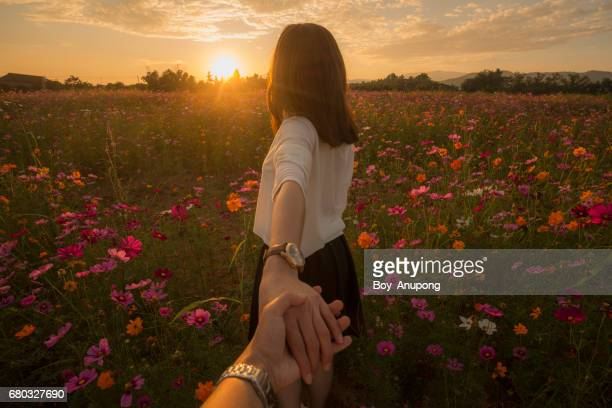 The couple travel and relax with the beautiful scenery view of Cosmos garden during the sunset in Chiang Rai, Thailand.