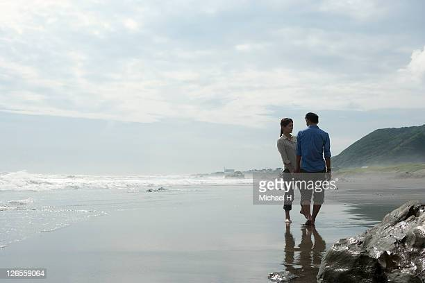 the couple who joins hands and talks on a beach - 千葉市 ストックフォトと画像
