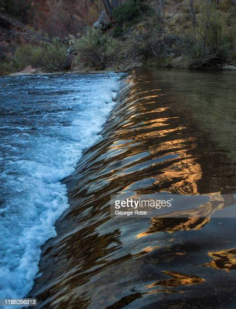 The Court of the Patriarchs rock formations are reflected on the Virgin River as viewed on November 9, 2019 in Zion National Park, Utah. Zion...