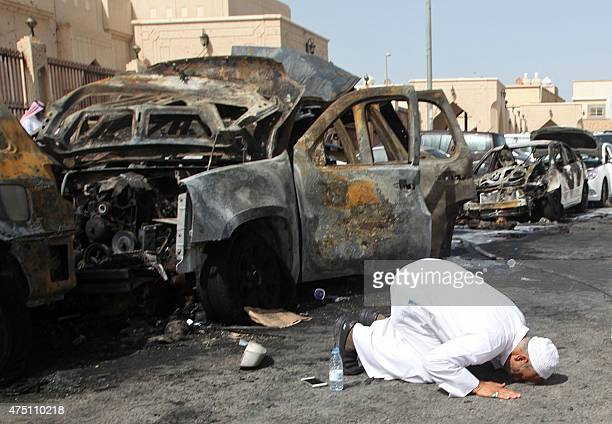 The cousin of a victim prays at the site of a suicide bombing that targeted the Shiite AlAnoud mosque in the Saudi coastal city of Dammam on May 29...