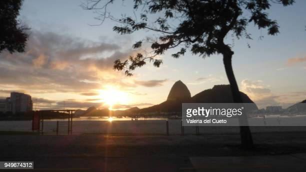 The cove of Botafogo and the sun rising behind the Sugar Loaf Mountain in Urca