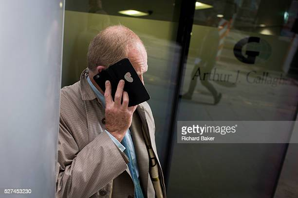 The cover of a smartphone obscures the face of a businessman in the City of London. Holding his handset to his ear, it hides his features making him...