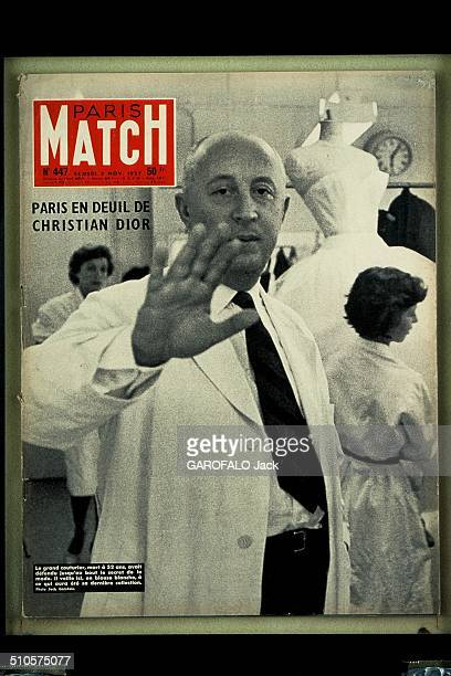 The cover of 'Paris Match' magazine no447 2nd November 1957 Christian Dior his hand toward the camera wearing a white coat and surrounded by workers...
