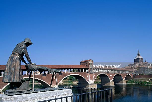 The covered bridge over the Ticino river built in 1949 to the original 14th century structure the Washerwomen Monument in the foreground Pavia...