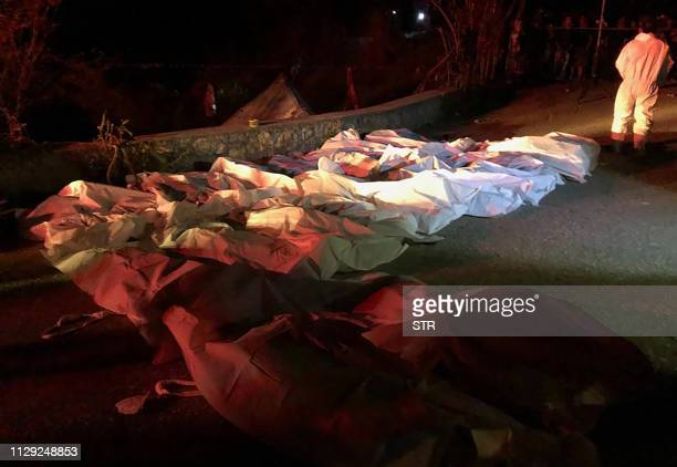 The covered corpses of Central American migrants killed when the truck in which they were riding ran off the road and overturned lie on the road near...