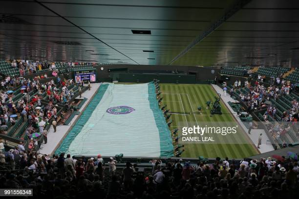 The covers are brought on as rain stops play between Croatia's Marin Cilic and Argentina's Guido Pella in their men's singles second round match on...