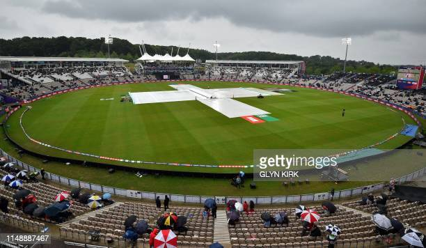 The covers are brought onto the field as rain stops play during the 2019 Cricket World Cup group stage match between South Africa and West Indies at...