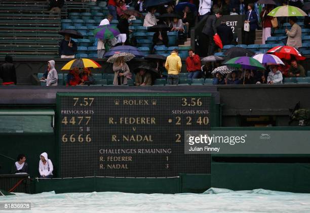 The covers come on at the second rain delay during the men's singles Final match on day thirteen of the Wimbledon Lawn Tennis Championships at the...