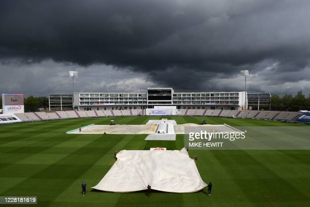 The covers start to come off under a threatening sky after a lengthy rain delay on the fourth day of the third Test cricket match between England and...