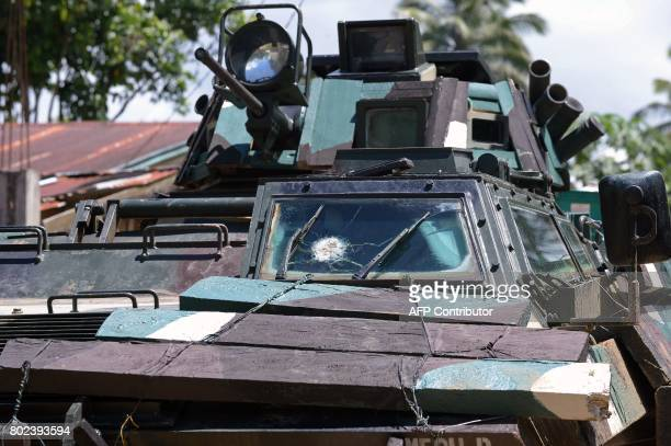 The cracked windshield of an armoured personnel carrier caused by a sniper bullet is seen as a military convoy heads to the frontline in the...