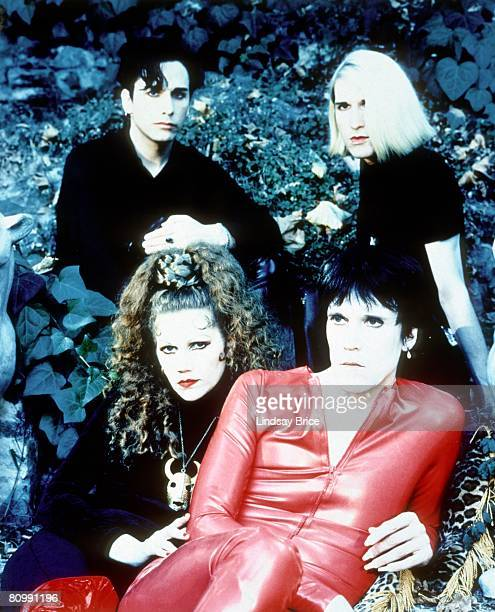 The Cramps Poison Ivy Rorschach in black with red boots and Lux Interior in red latex catsuit both seated upon garden step and backed by Harry...