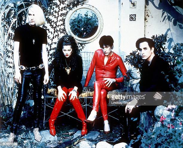 The Cramps Poison Ivy Rorschach in black with red boots and Lux Interior in red latex catsuit seated on garden bench between Slim Chance in cheetah...