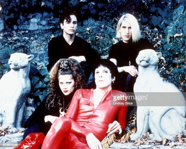 The Cramps Poison Ivy Rorschach in black with red boots and Lux Interior in red latex catsuit seated upon garden step flanked by lion figures and...
