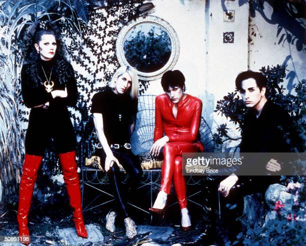 The Cramps Poison Ivy Rorschach stands left in black with red boots beside Slim Chance in black and Lux Interior in red latex catsuit both seated on...