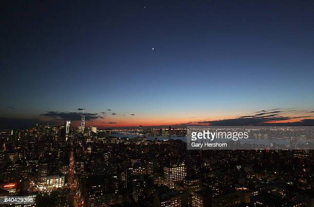 The crescent moon and Venus set above lower Manhattan as seen from the 56th floor of the Madison Square Park Tower on January 30, 2017 in New York...