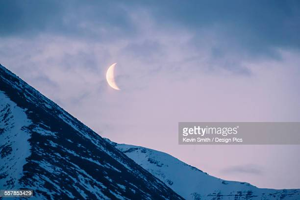 The crescent moon sets above the sentinal range along the alaska highway, muncho lake provincial park, northern canadian rockies