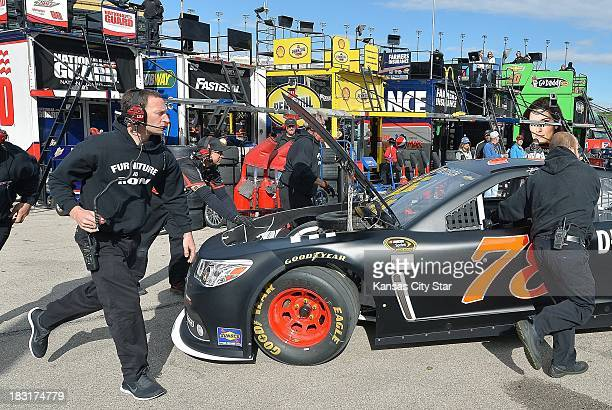 The crew for Sprint Cup Series driver Kurt Busch pulls out the team's backup car after the primary car was damaged hitting the wall during a practice...