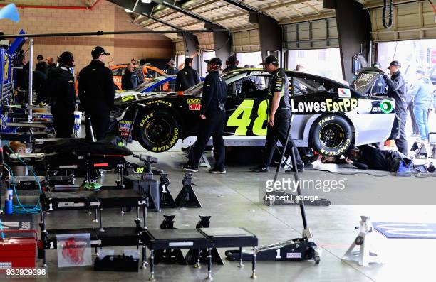 The crew for the Lowe's For Pros Chevrolet driven by Jimmie Johnson attempt to work on their car after failing inspection during qualifying for the...