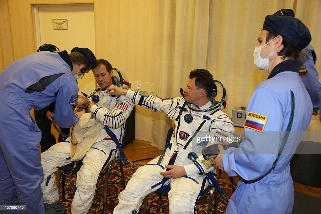 The crew members of the next expedition to the International Space Station (ISS), Russian cosmonaut Roman Romanenko (R) and US astronaut Tom Marshburn, put on their space suits during preflight preparation at the Russian leased Kazakhstan's Baikonur cosmodrome on December 7, 2012. Hadfield, Romanenko and Marshburn will join in December the remaining ISS crew, Russians Oleg Novitskiy and Evgeny Tarelkin, and Kevin Ford of the United States, who arrived there last month.